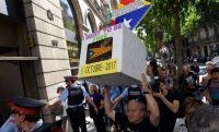 Un hombre sostiene una urna de cartón con una estelada frente al Tribunal Superior de Justicia de Barcelona. LLUIS GENE (AFP)