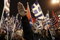 A supporter of Greece's extreme right party Golden Dawn raises his hand in a Nazi salute during a rally in Athens on Feb.1, 2014. (Yannis Kolesidis/AP)