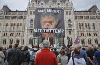 """A man holds a poster of Hungarian Premier Viktor Orban that reads """"What have I done again"""" during a protest by opposition parties against Orban's policies on migrants. (AP)"""