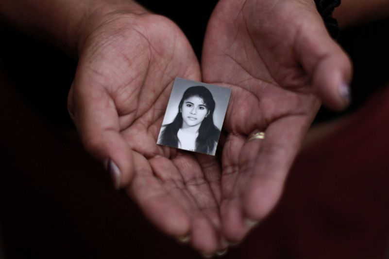 A relative with a photograph of Rosivel Elisabeth Grande, who was shot to death on her way to work in San Salvador in 2013. El Salvador is one of the world's deadliest countries for women. Credit Ulises Rodriguez/Reuters