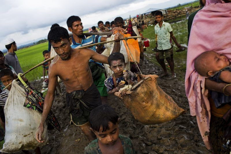 A Rohingya ethnic minority from Myanmar carries a child in a sack and walks through rice fields after crossing over to the Bangladesh side of the border near Cox's Bazar's Teknaf area, Friday, Sept. 1, 2017. Myanmar's military says almost 400 people have died in recent violence in the western state of Rakhine triggered by attacks on security forces by insurgents from the Rohingya. Advocates for the Rohingya, an oppressed Muslim minority in overwhelmingly Buddhist Myanmar, say hundreds of Rohingya civilians have been killed by security forces. Thousands have fled into neighboring Bangladesh. (AP Photo/Bernat Armangue) NYTCREDIT: Bernat Armangue/Associated Press