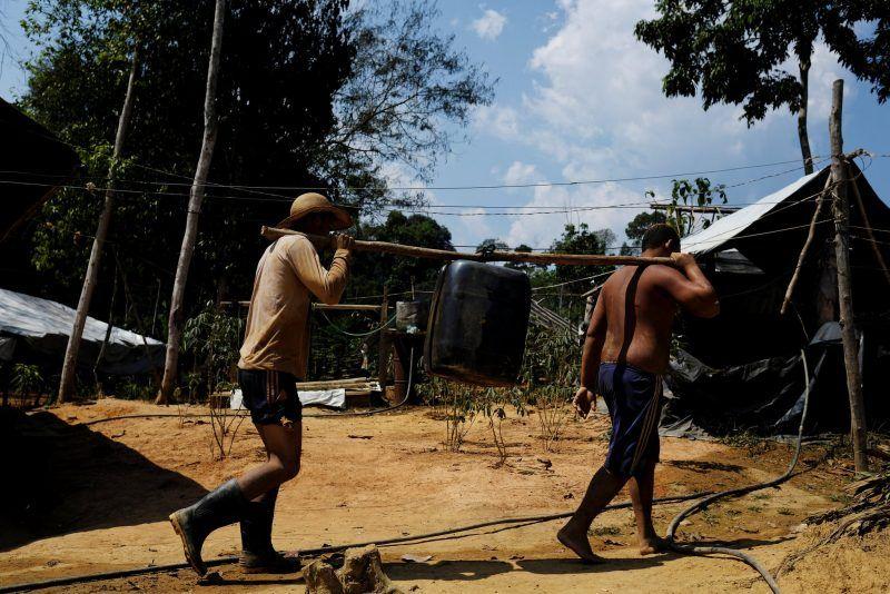 """Mineros ilegales, o """"garimpeiros"""", transportan un bidón de combustible diesel hasta una mina en el corazón selvático de la Amazonia brasilera cerca de Crepurizao, en el estado de Pará, el 6 de agosto de 2017. Credit Nacho Doce/Reuters"""