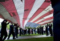 The National 9/11 Flag is unfurled during a ceremony on May 15, 2014, marking the opening of the National September 11 Memorial Museum in New York City. (Don Emmert/Agence France-Presse via Getty Images)