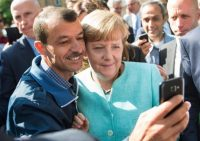 German Chancellor Angela Merkel has a selfie taken with a refugee during a visit to a refugee reception center in Berlin in September 2015. (EPA)