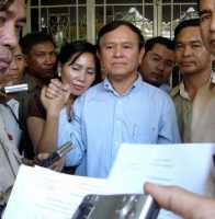 Kem Sokha held hands with his wife before his arrest in 2005 in Phnom Penh, Cambodia, on a charge of defamation. Credit Bunna Chor/Reuters