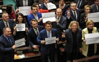 In this file photo, Poland's opposition party Nowoczesna leader Ryszard Petru (C) with other parliamentarians hold a card reading '#Free Media in Sejm' during a protest in Sejm, the lower house of the Polish parliament in Warsaw, Poland, December 16, 2016. The ruling Law and Order Party had proposed rules limiting news media access to the parliament. (EPA/MARCIN OBARA)