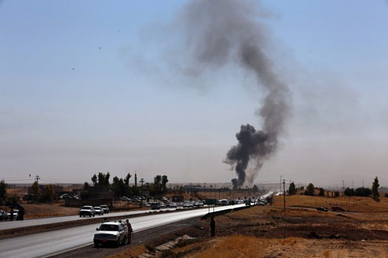 Smoke rises while Iraqi security forces use bombs as Kurdish security forces withdraw from a checkpoint on the outskirts of Irbil, Iraq, on Oct. 20. (Khalid Mohammed/Associated Press)