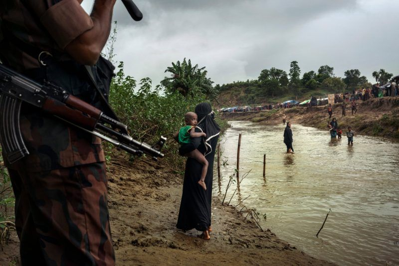A Bangladeshi border guard sending Rohingya back across the border into their makeshift camp in Myanmar in August. Credit Adam Dean for The New York Times