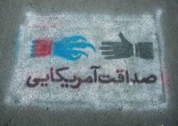 """Eric Lafforgue/Gamma-Rapho via Getty Images. A painting that reads, """"Honesty and friendship of America,"""" on the pavement near the former US embassy, Tehran, 2015"""
