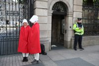 Niall Carson/AP Images. Reproductive rights activists, dressed as Handmaids from Margaret Atwood's The Handmaid's Tale, outside the Irish parliament before deliberation about the constitutional ban on abortion, September 18, 2017