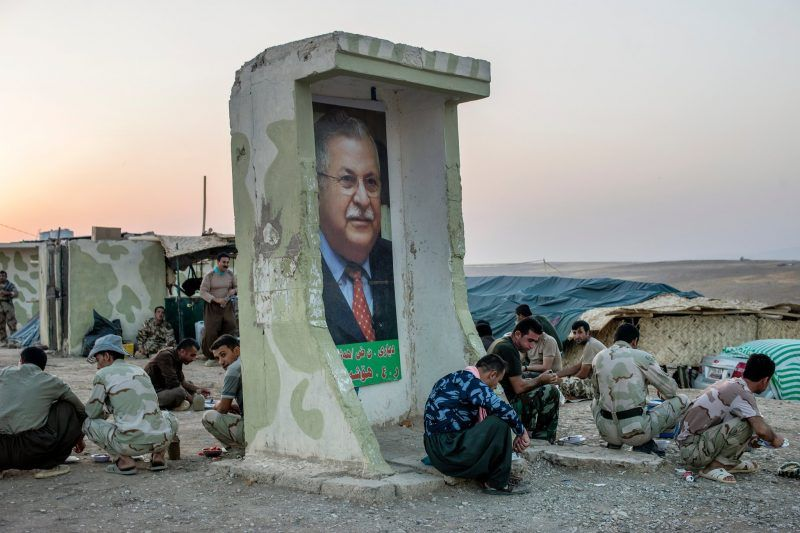Pesh merga troops near an image of Jalal Talabani, a Kurd and former Iraqi president, in 2014. Credit Andrea Bruce for The New York Times