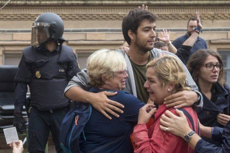 Varias personas lloran en el exterior del Instituto Can Vilumara de L'Hospitalet de Llobregat ante el despliegue policial. Quique García (EFE)