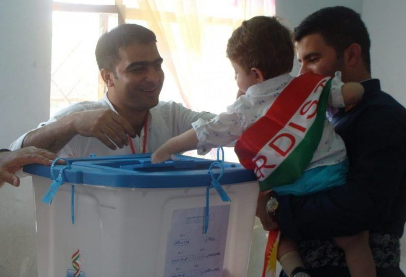 A child with a Kurdish flag is carried during the Sept. 25 referendum on regional independence in Halabja, Iraq. (Nicole Watts)