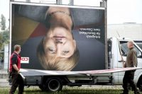 Workers remove an election poster of the Christian Democrats with a photo of German Chancellor Angela Merkel in Berlin, Monday, Sept. 25, 2017 after Sunday's parliament elections. Merkel faces a complicated quest to form a new government for Europe's biggest economy and find answers to the rise of a nationalist, anti-migrant party. (Wolfgang Kumm/dpa via AP)
