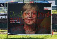 Pintada antiinmigrantes en un cartel electoral de Angela Merkel. MATTHIAS SCHUMANN (REUTERS)