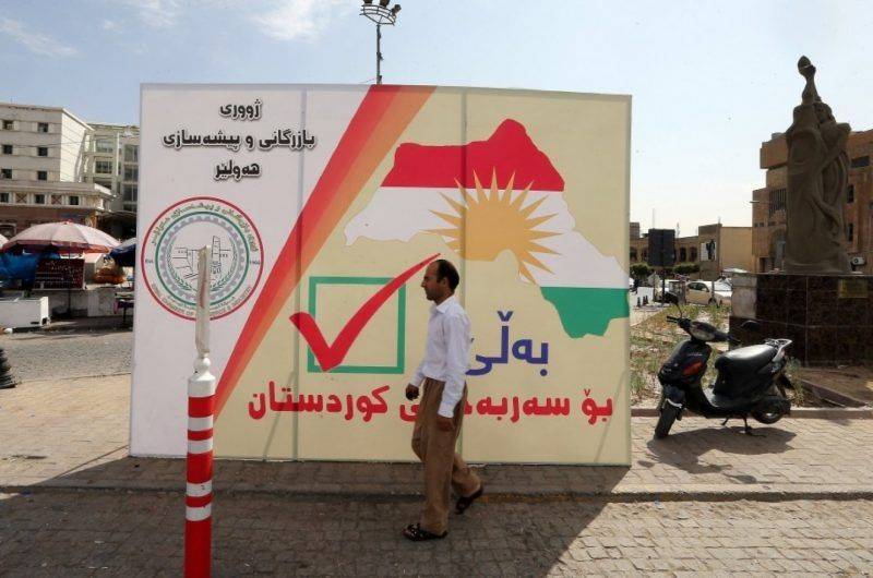 A man walks next to a poster in Irbil, in the Iraqi region of Kurdistan, that calls on Kurds to vote for independence on the eve of the Sept. 25 referendum. (Mohamed Messsara/European Pressphoto Agency/EFE)