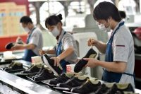 Workers assembling shoes in a factory in eastern China's Zhejiang province. The country will have to revise growth targets to prevent growing too quickly and becoming unstable. Credit CHINATOPIX, via Associated Press