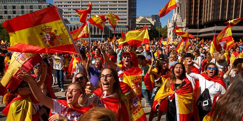 Demonstrators shout slogans and hold Spanish flags.