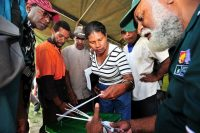 An electoral commission worker answers questions locals have on ballot boxes at a mock poll booth in Port Moresby before the 2012 elections in Papua New Guinea. (Australia Department of Defense/Flickr)