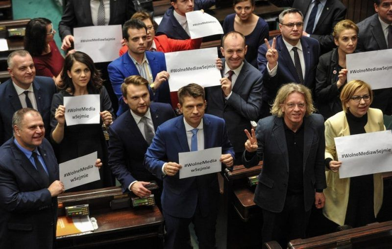 In December 2016, Ryszard Petru, center, leader of the opposition party Nowoczesna, holds a sign advocating press freedom along with other lawmakers during a protest in the Sejm, the lower house of the Polish Parliament in Warsaw. The opposition's occupation of the Parliament building ended Jan. 11. (Marcin Obara/EPA)