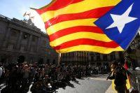 Un manifestante ondea la bandera independentista de Cataluña, o estelada, frente al Palacio de la Generalitat el 30 de octubre, en el primer día de trabajo luego de la invocación del artículo 155 de la Constitución de España. Credit Javier Etxezarreta/European Pressphoto Agency