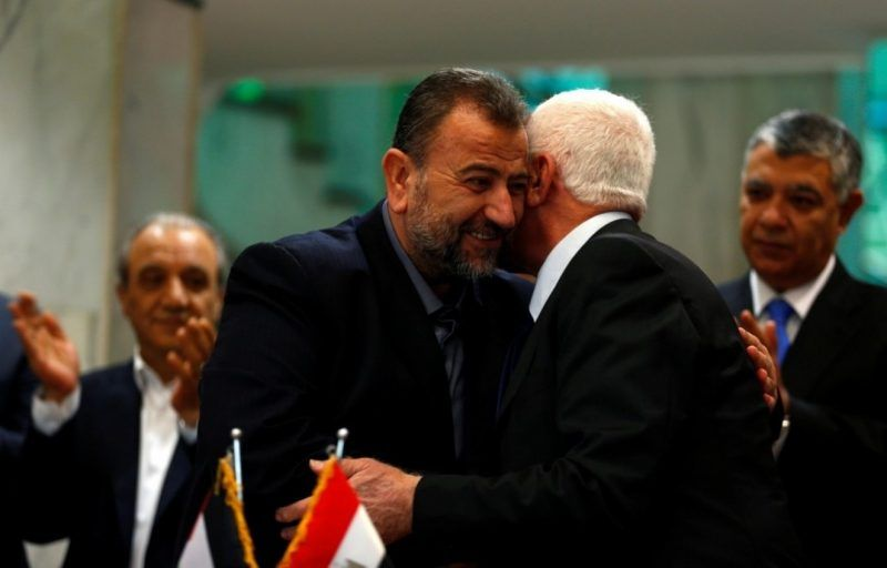 Saleh Arouri, left, head of the Hamas delegation, hugs Fatah leader Azzam Ahmad as they sign a reconciliation deal in Cairo on Oct. 12. (Amr Abdallah Dalsh/Reuters)