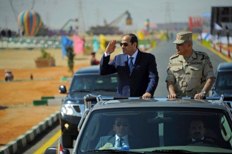 Egyptian President Abdel-Fattah al-Sissi salutes as he inspects troops with Defense Minister Sedki Sobhy in Suez, Egypt, on Oct. 29. Egypt launched a major shakeup of its security services on Saturday in an apparent reaction to an ambush by militants outside Cairo a week earlier that killed at least 16 troops. (MENA via AP)