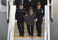 Yang Xiuzhu is escorted from a plane upon arriving at the Beijing Capital International Airport. The former vice mayor and China's most-wanted fugitive is accused of corruption and was arrested after returning from the United States. (Yin Gang/Xinhua/AP)