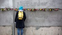 Una joven ante el muro de Berlín. OMER MESSINGER Agencia EFE