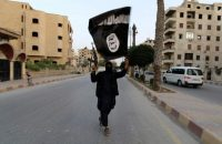 A member loyal to the Islamic State in Iraq waves an Islamic State flag in Raqqa in 2014. (Reuters)
