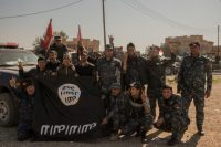 Iraqi federal police officers hold up a captured Islamic State flag in the village of Abu Saif, about four miles from Mosul, on Feb. 22, 2017, in Nineveh province, northern Iraq. (Martyn Aim/Getty Images)