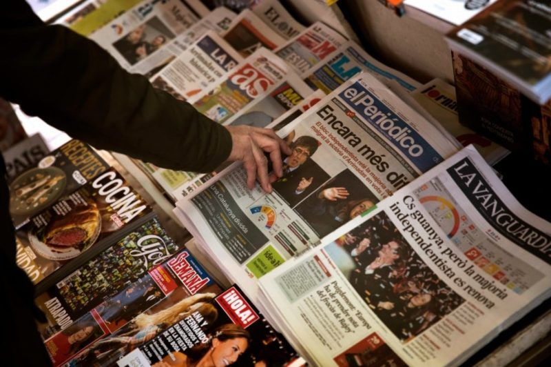 A man buys a newspaper featuring the results at the Catalan regional election at a news stand in Barcelona on Dec. 22. (Emilio Morenatti/Associated Press)