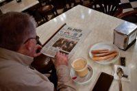 Un hombre lee en el periódico los resultados de las elecciones catalanas mientras toma el desayuno el viernes 22 de diciembre, en Pamplona, al norte de España. Las elecciones han fallado en ofrecer más claridad sobre el destino del conflicto independentista catalán. Credit Alvaro Barrientos/Associated Press