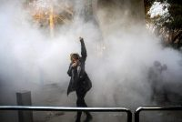 A woman dodged tear gas at Tehran University on Saturday, the third day of unauthorized protests in Iran. Credit via Associated Press