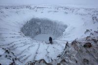 Un integrante de una expedición se aproxima al borde de un cráter en el norte de Siberia. Credit Reuters
