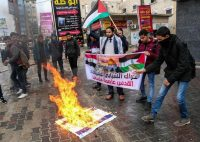 """Palestinian protesters burn a picture of US President Donald Trump and the Israeli flag in the southern Gaza Strip town of Rafah on December 6, 2017. The slogan in Arabic reads: """"Palestinian youth protest movement Jerusalem is the capital of Palestine"""". President Donald Trump is set to recognise Jerusalem as Israel's capital, upending decades of careful US policy and ignoring dire warnings from Arab and Western allies alike of a historic misstep that could trigger a surge of violence in the Middle East. / AFP PHOTO / SAID KHATIBSAID KHATIB/AFP/Getty Images."""
