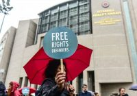 A protester holds a placard during a rally outside the courthouse where the trial of 11 human rights activists was taking place in Istanbul on Oct. 25. (Yasin Akgul/AFP/Getty Images)