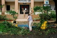 A resident sweeping leaves and branches in front of her building in San Juan, P.R., after Hurricane Irma struck. Credit Erika P. Rodriguez for The New York Times