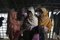 Rohingya women cry while watching a graphic video of the Tula Toli massacre in their home in Thaingkhali Rohingya refugee camp in Bangladesh in December. (Allison Joyce for The Washington Post)