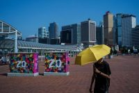 A lone yellow umbrella, the symbol of the Umbrella Movement in 2014, among placards last May marking the 20th anniversary of the return of Hong Kong to China. Credit Lam Yik Fei for The New York Times