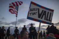 """Police form a line on the boardwalk to keep demonstrators and counter demonstrators apart during an """"America First"""" demonstration in August in Laguna Beach, Calif. (Getty Images)"""