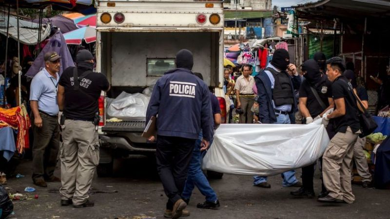Police investigators carry a body to a forensic vehicle, after a shootout between private security guards and gang members, at the central market in San Salvador, El Salvador on March 15, 2017. (Salvador Melendez / Associated Press)