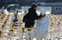 On Dec. 27, a woman puts a scarf on a statue of a comfort woman sitting in an installation of empty chairs symbolizing the victims in Seoul. (AP)