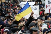 Protesters hold the Ukraine flag and anti-government signs at a rally in downtown Kiev, Ukraine, on Dec. 17, demanding that lawmakers lift their parliamentary immunity and establishment an anti-corruption court. (EPA-EFE/Shutterstock)