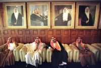 Saudi subjects sit under portraits of King Fahd, left, and his predecessors which adorn the walls of the National Guard headquarters in Riyadh, Feb. 26, 1997. (John Moore/AP)