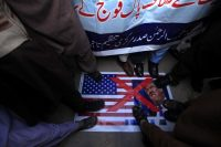 Protesters step on an image of the United States flag and President Trump in Peshawar, Pakistan, this month. Credit Arshad Arbab/European Pressphoto Agency