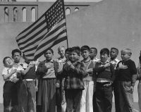 Children pledge allegiance to the U.S. flag at Raphael Weill Public School, San Francisco, in the early 1940s. (U.S. National Archives and Records Administration)