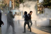 Iranian students run from tear gas during a demonstration at the University of Tehran on Dec. 30. (Agence France-Presse via Getty Images)