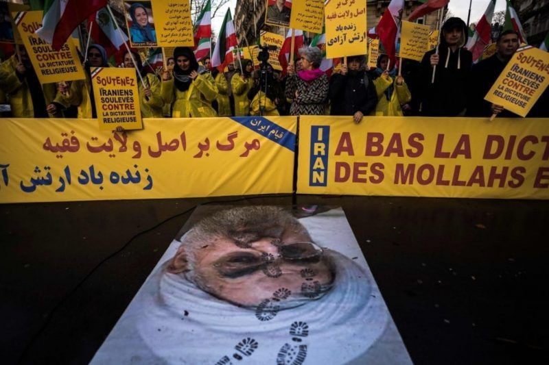 """Protesters hold placards reading """"Support Iranians risen up against the religious dictatorship"""" as they stand behind a portrait of Iranian President Hassan Rouhani with shoe marks over it, in Paris on Wednesday. (Lionel Bonaventure/AFP via Getty Images)"""