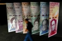 A man walks past banners depicting Venezuela's currency, the bolivar, at the Central Bank of Venezuela in Caracas. (AFP/Getty Images)